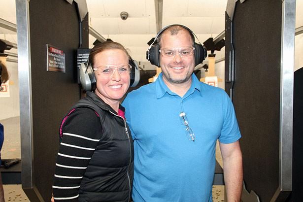 Couple standing in front of shooting range.